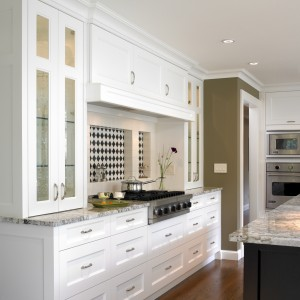 A graphic black and white backsplash pattern pulls the black stained island and the white perimeter cabinetry together
