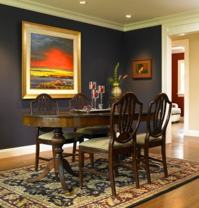 A deep eggplant creates an elegant and striking backdrop for a vibrant piece of art. Notice the effect of the dark red wall in the media room in the back, and how your eye travels from the painting to that room and back